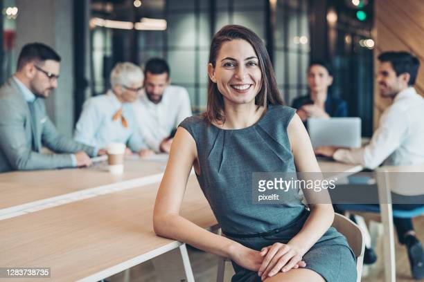 smiling businesswoman sitting in front of her colleagues - executive director stock pictures, royalty-free photos & images