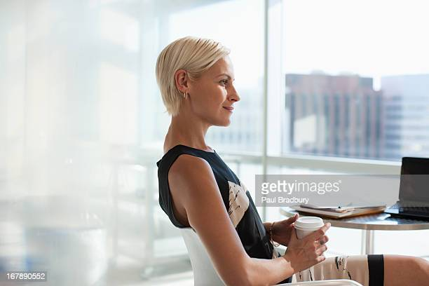smiling businesswoman sitting in office - mid adult women stock pictures, royalty-free photos & images