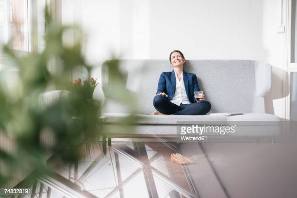 Smiling businesswoman sitting on couch with beverage