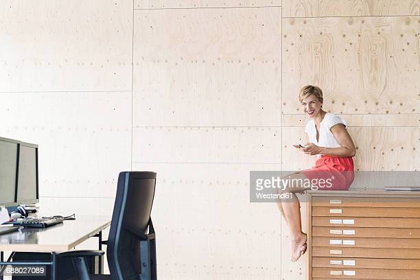 Smiling businesswoman sitting on filing cabinet in creative office