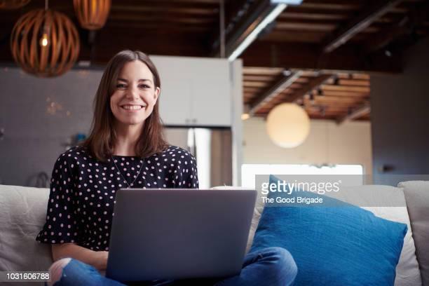 smiling businesswoman sitting on sofa in creative office - computer - fotografias e filmes do acervo