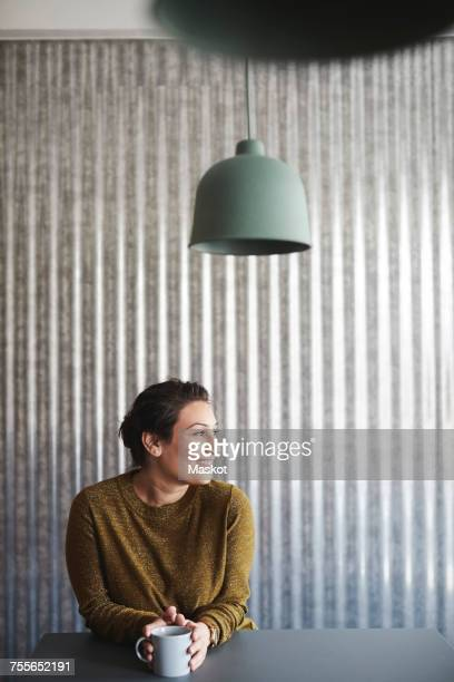 Smiling businesswoman sitting with coffee cup at desk against corrugated iron wall