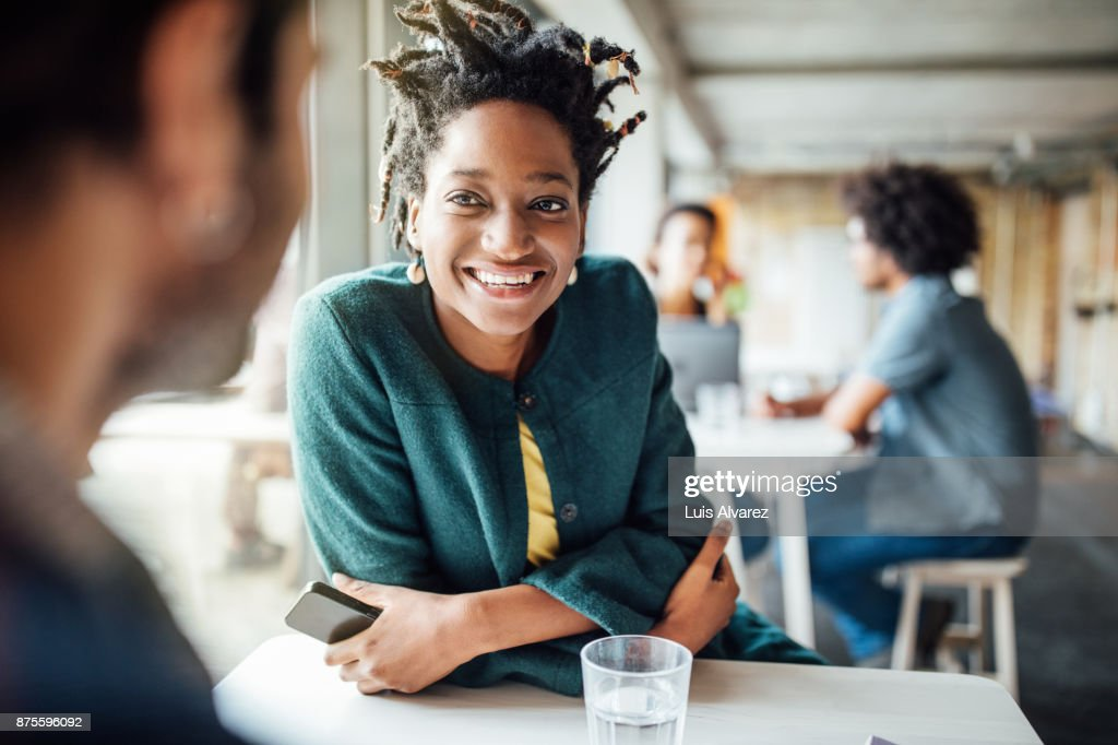 Smiling businesswoman sitting with colleague in cafeteria : Photo