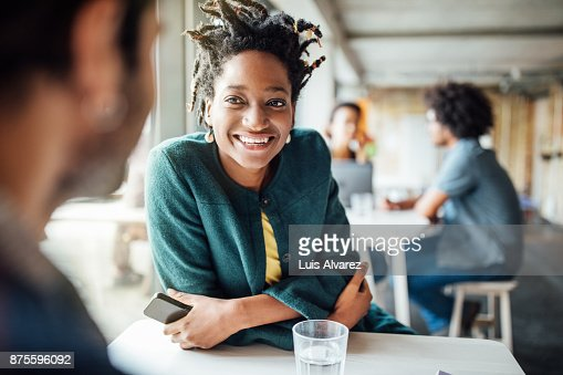 Smiling businesswoman sitting with colleague in cafeteria