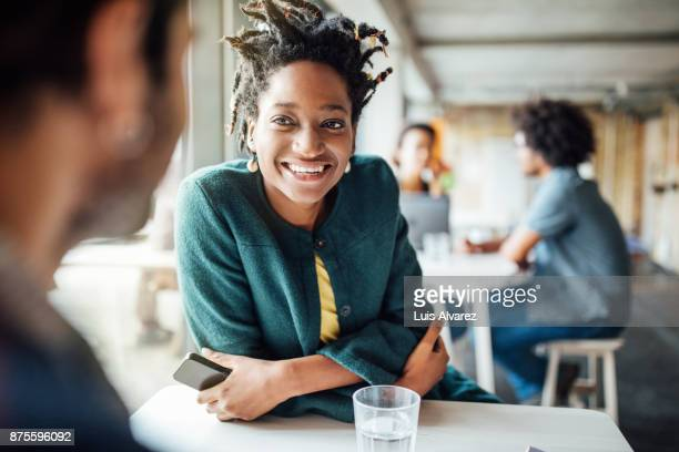 smiling businesswoman sitting with colleague in cafeteria - business finance and industry stock pictures, royalty-free photos & images