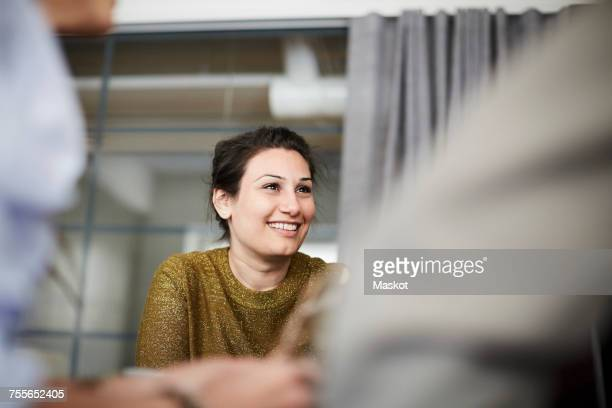 Smiling businesswoman sitting with colleagues in board room during meeting