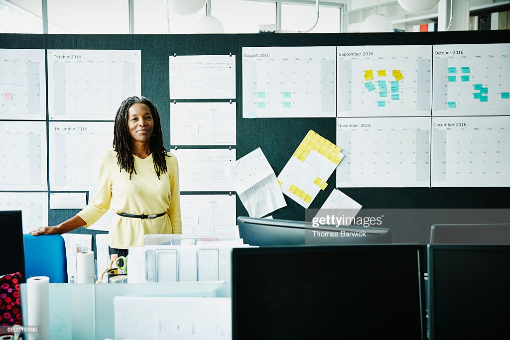 Smiling businesswoman standing at workstation : Stock Photo