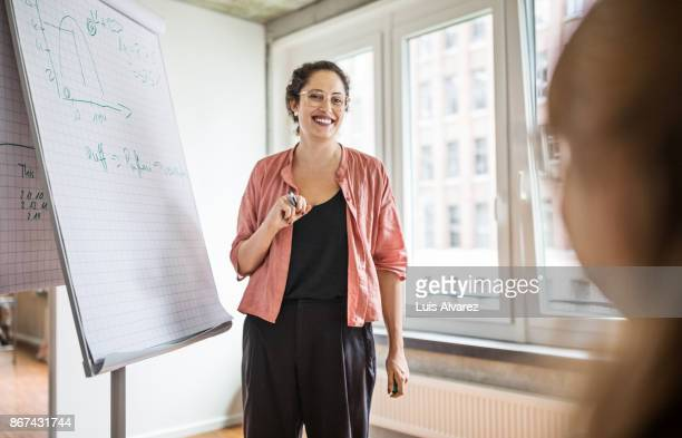 smiling businesswoman standing by flip chart in creative office - vanguardians stock pictures, royalty-free photos & images
