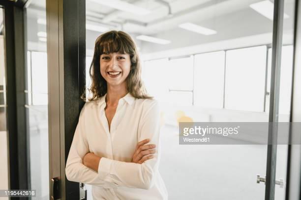 smiling businesswoman standing in an open office door - open blouse - fotografias e filmes do acervo