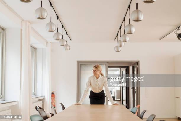 smiling businesswoman standing in conference room - three quarter front view stock pictures, royalty-free photos & images