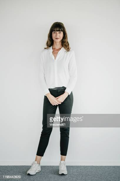 smiling businesswoman standing in front of a white wall - vêtement de peau photos et images de collection