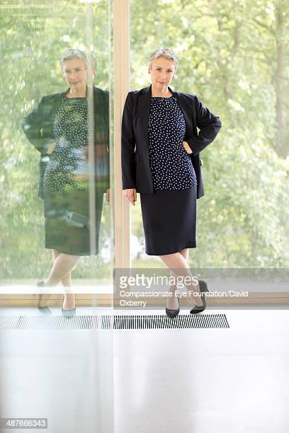 Smiling businesswoman standing in office hallway