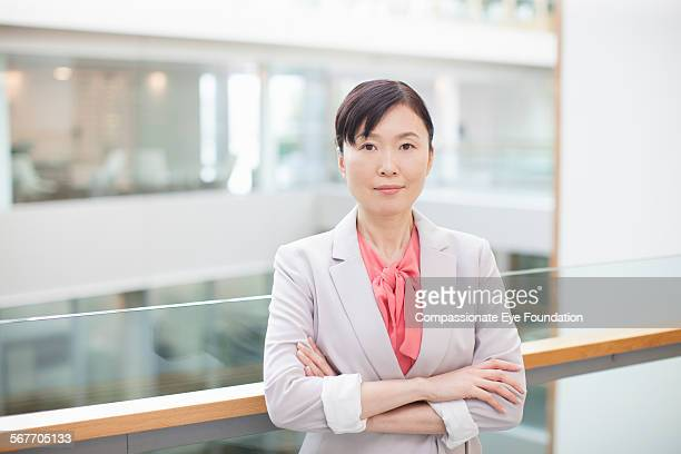 Smiling businesswoman standing on atrium balcony