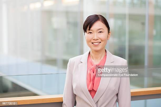 smiling businesswoman standing on atrium balcony - ジャケット ストックフォトと画像