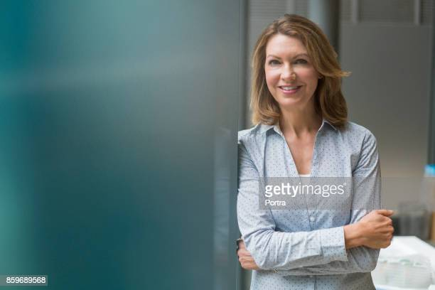 smiling businesswoman standing with arms crossed - waist up stock pictures, royalty-free photos & images
