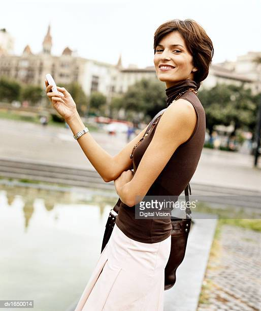 smiling businesswoman stands in a urban setting, holding a mobile phone - sleeveless top stock pictures, royalty-free photos & images