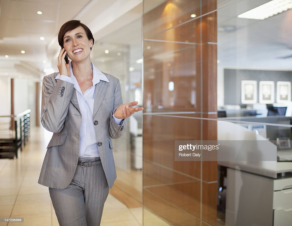 Smiling businesswoman talking on cell phone in office corridor : Stock Photo