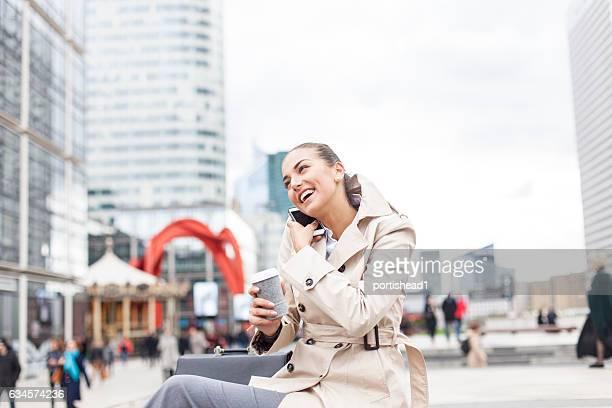 Smiling businesswoman talking on smart phone on street