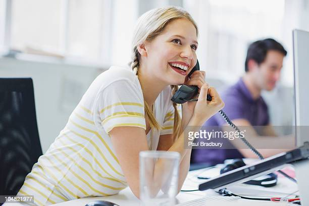 Find a picture of a girl talking on a landline phone.what section is this picture in