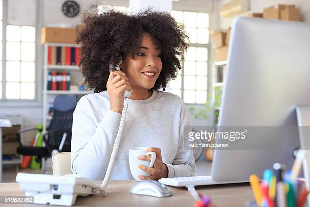 Smiling businesswoman talking on the landline phone
