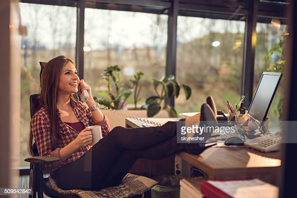 Smiling businesswoman talking on the phone during coffee break.