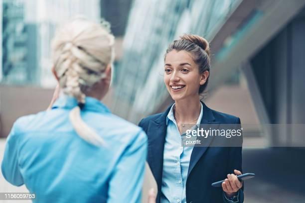 mulher de negócios de sorriso que fala a um colega - coque cabelo para cima - fotografias e filmes do acervo