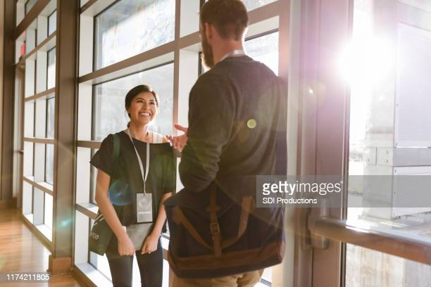 smiling businesswoman talking with friend during seminar - summit meeting stock pictures, royalty-free photos & images