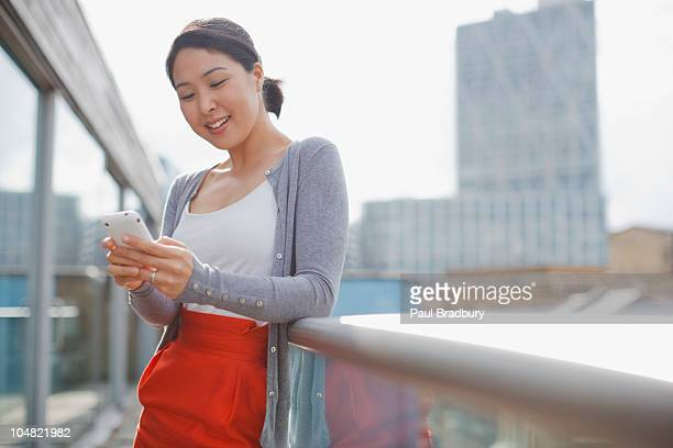 smiling businesswoman text messaging with cell phone on urban balcony - korean ethnicity stock pictures, royalty-free photos & images