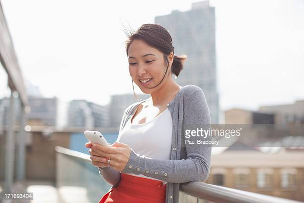 Smiling businesswoman text messaging with cell phone on urban balcony