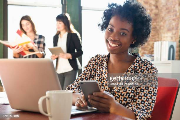 smiling businesswoman using cell phone and laptop in office - personne secondaire photos et images de collection