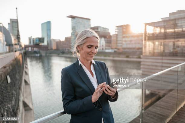Smiling businesswoman using cell phone on bridge