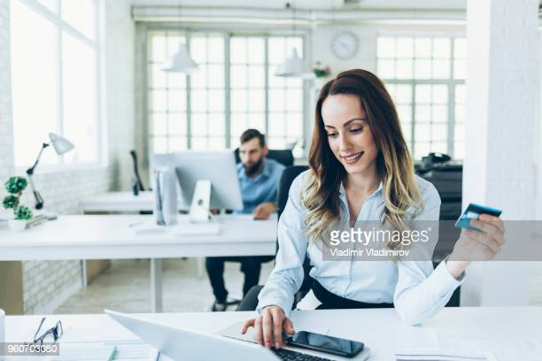 Smiling businesswoman using credit card at work