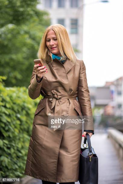 Smiling businesswoman using her mobil phone while walking on the street