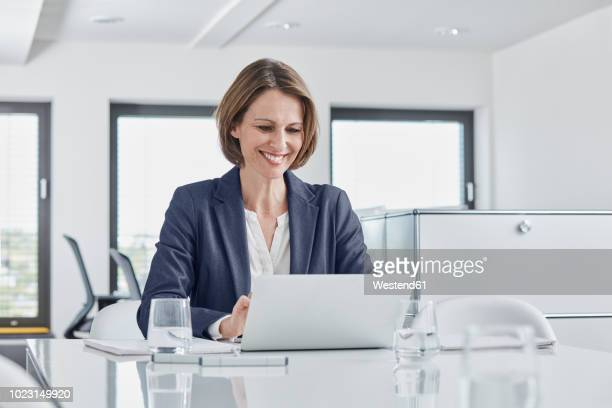 smiling businesswoman using laptop at desk in office - directrice photos et images de collection