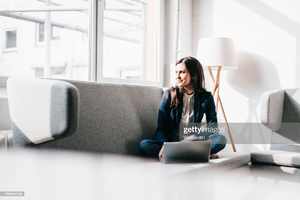 Smiling businesswoman using laptop on couch : Stock Photo