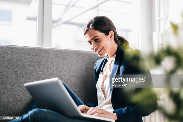 Smiling businesswoman using laptop on couch