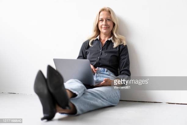 smiling businesswoman using laptop while sitting on floor against wall in office - businesswear stock pictures, royalty-free photos & images