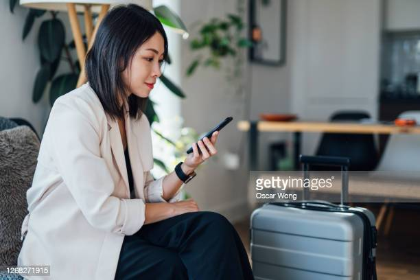 smiling businesswoman using mobile phone at home - waiting stock pictures, royalty-free photos & images
