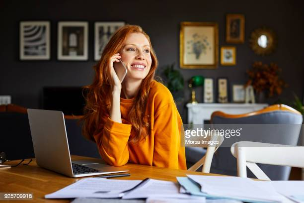 lächelnde geschäftsfrau mit handy am tisch - arbeitszimmer stock-fotos und bilder