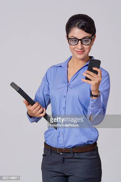 Smiling businesswoman using mobile phone while holding laptop against gray background