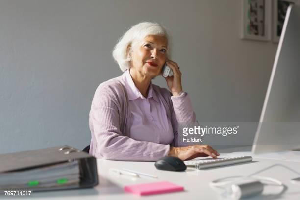 smiling businesswoman using mobile phone while working on computer at office - eine seniorin allein stock-fotos und bilder