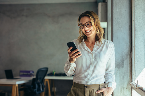 Smiling businesswoman using phone in office 1153863127