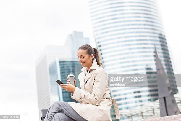 Smiling businesswoman using smart phone on street