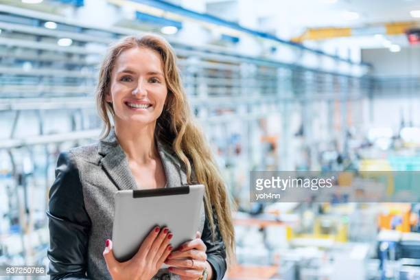 smiling businesswoman using tablet at factory - beautiful czech women stock photos and pictures
