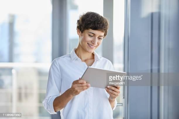 smiling businesswoman using tablet at the window in office - weibliche angestellte stock-fotos und bilder