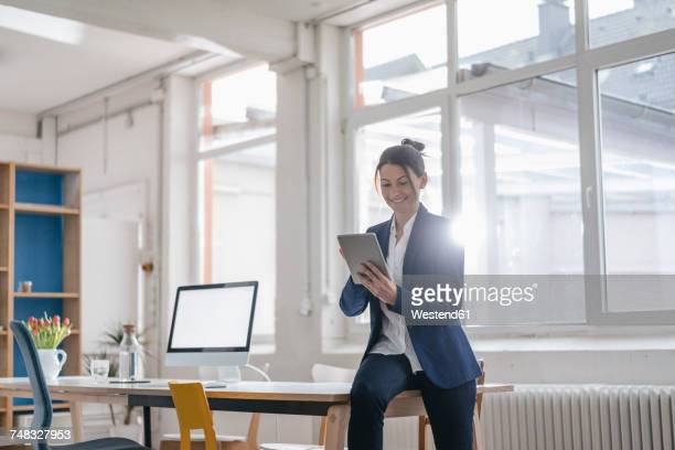 Smiling businesswoman using tablet in a loft