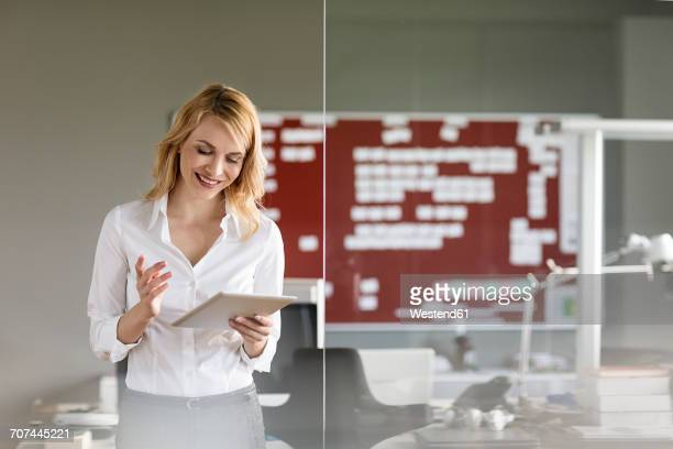 smiling businesswoman using tablet in office - regarder vers le bas photos et images de collection