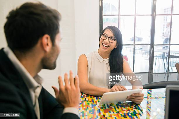Smiling businesswoman using tablet PC by coworker