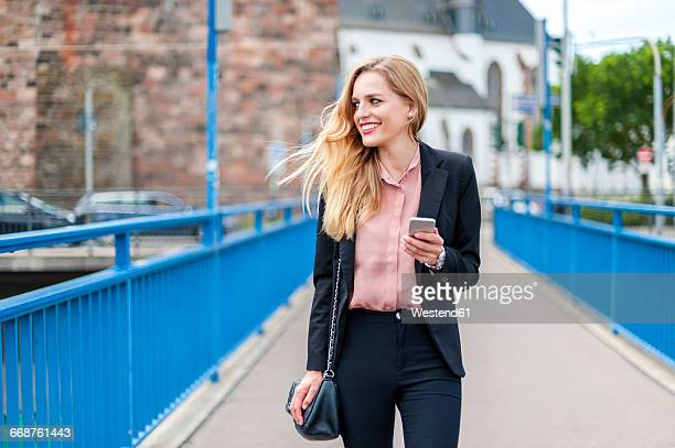 smiling businesswoman walking on a bridge looking at her smartphone - blazer foto e immagini stock