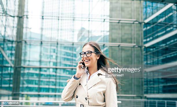 Smiling businesswoman walking on street and talking on smart phone